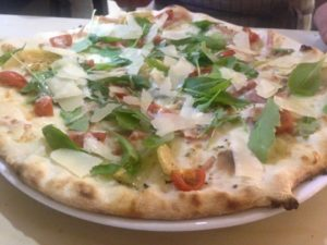 Mozzarella, tomate cherry, rucula, alcachofas, bacon y láminas de parmigiano